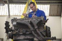 Mecânico usando chave no motor do carro na garagem de reparação — Fotografia de Stock