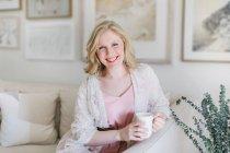 Young woman sitting on sofa and holding coffee mug — Stock Photo