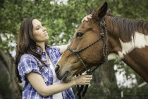 Portrait of young woman, petting horse — Stock Photo