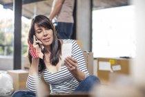 Femme dans la chambre regardant des échantillons de couleur et utilisant un smartphone — Photo de stock