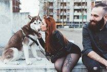 Rothaarige Frau küsst Hund — Stockfoto