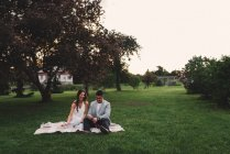 Romántico joven pareja abriendo el champán rosado en el parque al atardecer - foto de stock