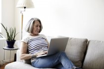 Senior woman reclining on sofa and typing on laptop — Stock Photo