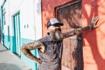 Hipster mâle tatoué, appuyé contre le mur ensoleillé — Photo de stock
