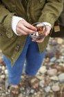 Женщина на галечный пляж, холдинг свежие орехи — стоковое фото