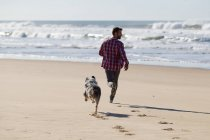 Man running with dog on sandy beach — Stock Photo