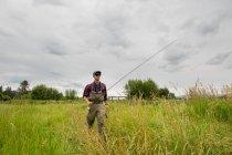 Рыбак с удочкой прогуливается по травяному полю, Кларк-Форк, Монтана — стоковое фото
