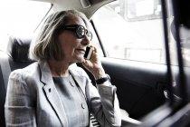 Старшая деловая женщина сидит на заднем сиденье такси, используя смартфон — стоковое фото