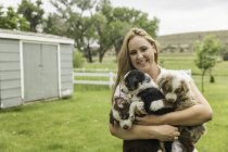 Portrait of young woman carrying three puppies in arms on ranch, Bridger, Montana, USA — Stock Photo