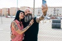 Maduro hipster pareja tomando selfie por alambre cerca - foto de stock