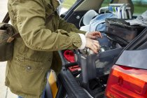 Молода жінка, видалення речі з багажника автомобіля — стокове фото