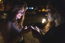 Friends at night illuminated by light of telephones — Stock Photo