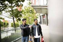Deux jeunes hommes en passant devant les magasins et en pointant dans la vitrine — Photo de stock