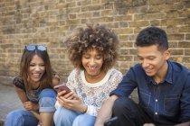 Tre amici sorridenti che guardano lo smartphone seduti in strada — Foto stock