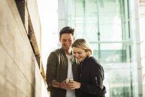 Giovane coppia in città a guardare smartphone — Foto stock