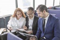 Молодая предпринимательница и бизнесмены рассматривают документы на пассажирском пароме — стоковое фото