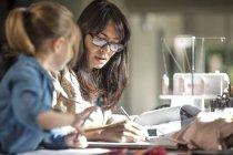Зрелая женщина занимается бумажной работой, пока дочь рисует за столом. — стоковое фото