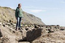 Woman on rocky coast looking at sea — Stock Photo