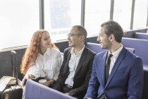 Молодая предпринимательница и бизнесмены разговаривают на пассажирском пароме — стоковое фото