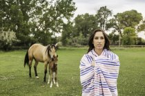 Portrait of young woman wrapped in blanket, horse and foal in background — Stock Photo