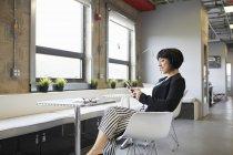 Бізнес-леді за допомогою смартфона на столі в офісі — стокове фото