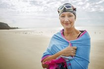 Donna con avvolgere sulle spalle sulla spiaggia — Foto stock