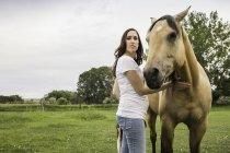 Портрет молодої жінки, стоячи з конем — стокове фото