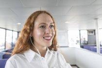 Femme souriante écoutant de la musique dans les écouteurs sur le ferry de passagers — Photo de stock