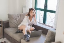 Young woman sitting on sofa using laptop and making smartphone call — Stock Photo