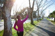 Visão traseira da mulher tomando selfie na rua — Fotografia de Stock