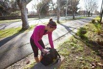 Mujer joven en la calle buscando a través de la mochila - foto de stock