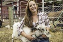 Портрет молодой женщины, ласкающей козу на ранчо, Бриджер, Монтана, США — стоковое фото