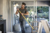 Man in unfurnished home holding paint roller — Stock Photo