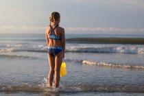 Vista posterior de chica en la playa sosteniendo el cubo, North Myrtle Beach, Carolina del sur, Estados Unidos, Norteamérica - foto de stock
