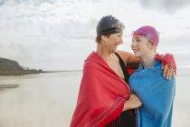 Madre e hija en playa con mantones - foto de stock