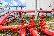 Robinets de tuyauterie industriels rouges à l'usine de biocarburant — Photo de stock
