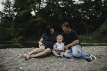 Pregnant couple sitting on beach with male toddler son, Lake Ontario, Canada — Stock Photo