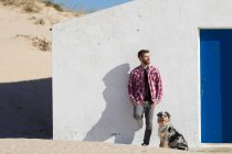 Man with dog leaning against wall at beach — Stock Photo
