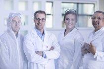 Ritratto di quattro operai di laboratorio in laboratorio — Foto stock