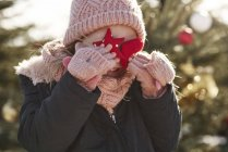 Girl in christmas tree forest covering her eyes with christmas decorations — Stock Photo