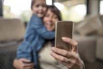 Foco superficial de la mujer madura tomando selfie con hija - foto de stock