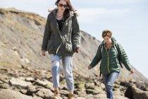 Madre e figlia camminano sulle rocce in riva al mare — Foto stock