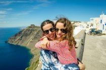 Mère et fille serrait et souriant à la caméra, Santorin, Kikladhes, Grèce — Photo de stock