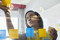 Young woman in office sticking notes to glass in office — Stock Photo