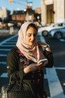 Mulher jovem em hijab olhando para smartphone ao ar livre — Fotografia de Stock
