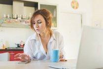 Молодая женщина на кухонном столе, глядя на смартфон — стоковое фото