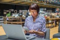 Жінка користується смартфоном і лептопом у кафе — стокове фото