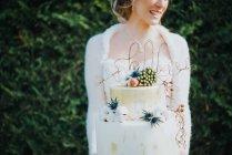 Невеста держит свадебный торт на заднем плане — стоковое фото