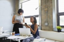 Zwei Kollegen mit Smartphone und Laptop im Büro — Stockfoto