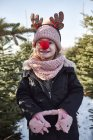 Girl in christmas tree forest with red nose, portrait — Stock Photo